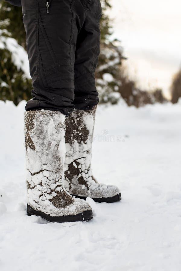 Füße in warmem, bequem glaubten, dass Schuhe mit dem Schnee, der an ihnen nach einem Weg durch die Schneewehen im Wald festgehalt stockfoto