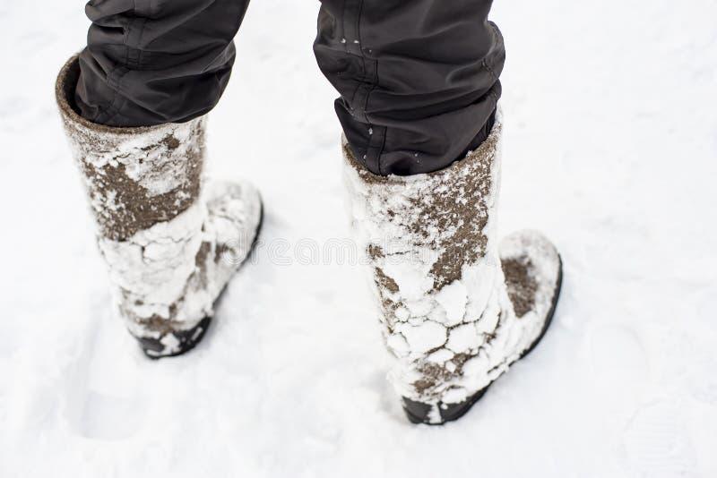 Füße in warmem, bequem glaubten, dass Schuhe mit dem Schnee, der an ihnen nach einem Weg durch die Schneewehen im Wald festgehalt lizenzfreie stockbilder