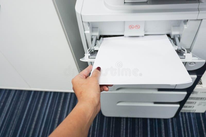 Fügen Sie Papier in den Drucker ein stockfotografie