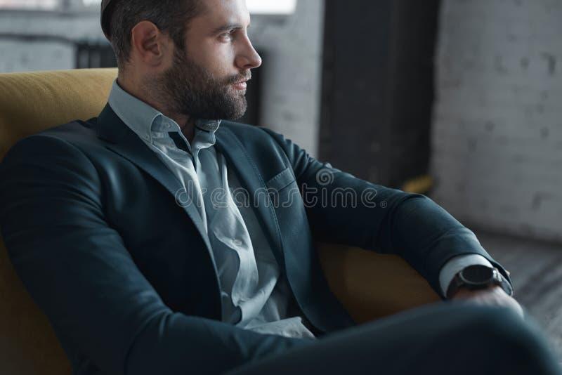 Fühlen bequem in seiner Art Draufsicht des hübschen jungen Mannes in der vollen Klage, die beim Sitzen auf dem Sofa weg schaut lizenzfreie stockfotos