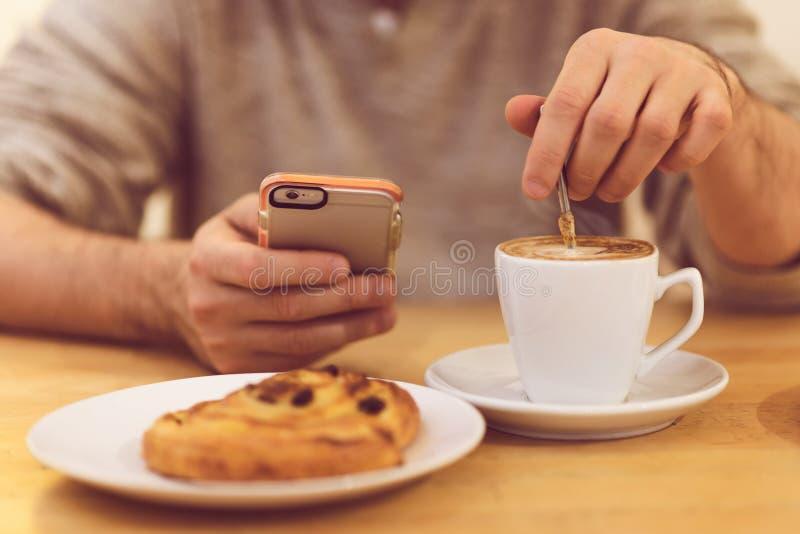 Führen Sie Bild des trinkenden Kaffees und des Haltens des unrecognisable Mannes des intelligenten Telefons beim Frühstücken im R stockfotografie