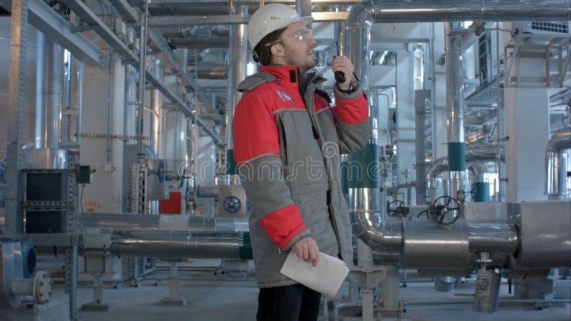 Führen Sie das Arbeiten in einem Wärmekraftwerk mit der Unterhaltung auf dem Funksprechgerät für Kontrollearbeit aus stockfotografie