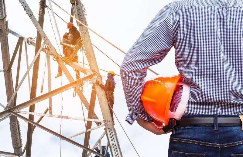 Führen Sie das Halten des gelben Schutzhelms mit den Elektrikern aus, die an Pylonbauturm arbeiten stockfotografie