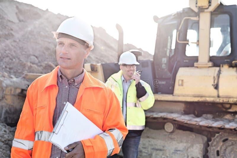 Führen Sie das Halten des Klemmbrettes auf Baustelle mit Kollegen im Hintergrund aus stockbild