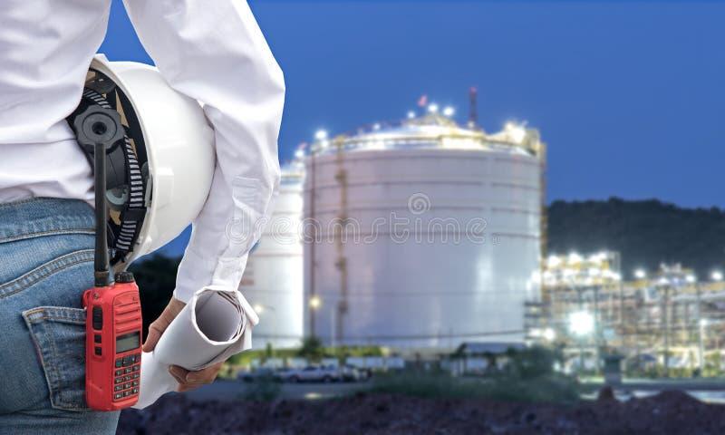 Führen Sie die Frau aus, die weißen Sturzhelm und Plan mit Radio für Arbeitskraftsicherheitskontrolle an der Kraftwerkenergiewirt lizenzfreies stockbild