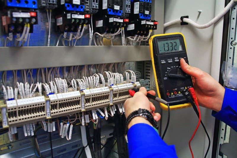 Führen Sie industrielle elektrische Stromkreise der Tests mit einem Vielfachmessgerät im Steueranschlusskasten aus lizenzfreie stockbilder