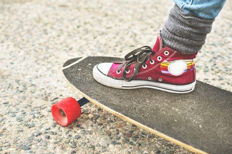 Führen Sie Longboard einzeln auf, das mit den Beinen eines Mädchens in den Turnschuhen teilweise groß ist lizenzfreies stockfoto