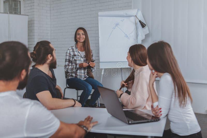 Führende Sitzung der schönen jungen Geschäftsfrau im Büro lizenzfreies stockfoto