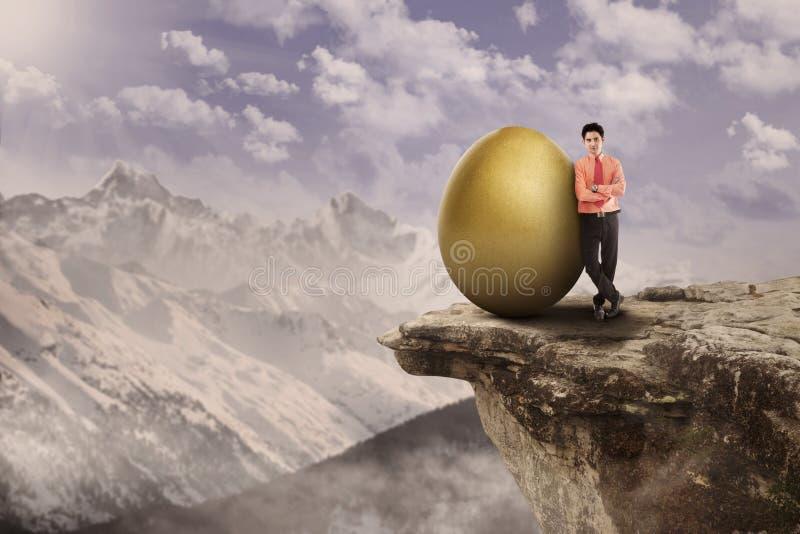 Führender Vertreter der Wirtschaft und goldenes Ei auf die Oberseite stockfotografie