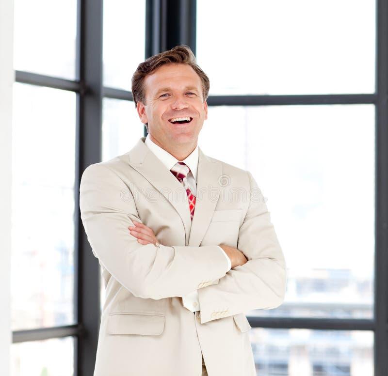 Führender Vertreter der Wirtschaft mit den gefalteten Armen lächelnd am Ca lizenzfreies stockfoto