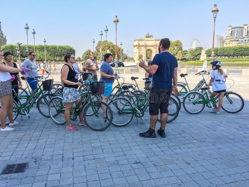 Führer bereitet Touristen für eine Fahrradreise mitten in Paris, nahe dem Louvre-Museum vor lizenzfreie stockfotografie