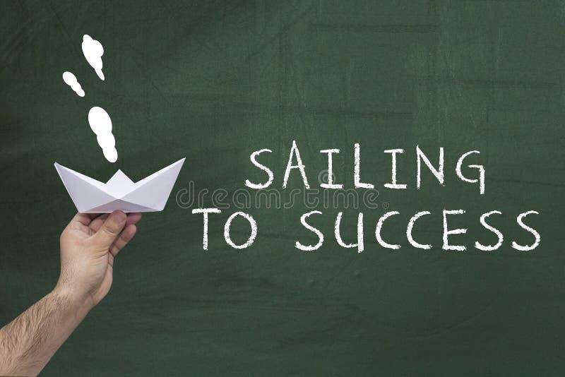 Führung, Geschäft, Erfolgskonzept Menschliche Hand, die Papierboot gegen grüne Tafel mit Text hält: Segeln zum Erfolg lizenzfreies stockbild