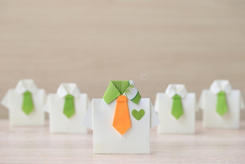 Führung und Teamwork-Konzept, gelbes Hemd des Origamis mit Bindung und Führung unter kleinem gelbem Hemd auf wooder Hintergrund stockbilder