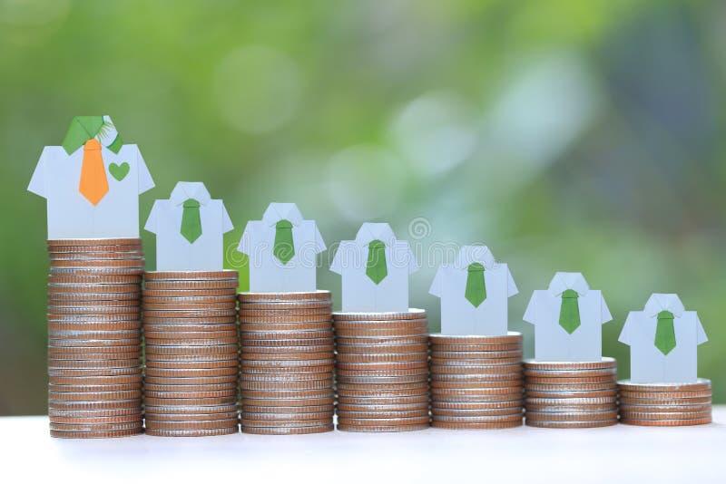 Führung und Teamwork-Konzept, grünes Hemd des Origamis auf wachsendem Stapel Münzengeld auf natürlichem grünem Hintergrund lizenzfreie stockfotografie