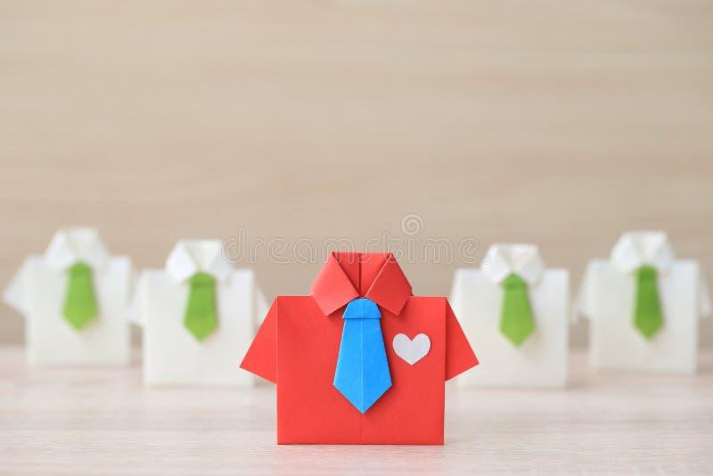 Führung und Teamwork-Konzept, rotes Hemd des Origamis mit Bindung und Führung unter kleinem gelbem Hemd auf wooder Hintergrund stockfoto