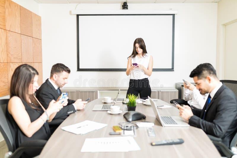 Führungskräfte, die Handys in der Sitzung verwenden stockbild