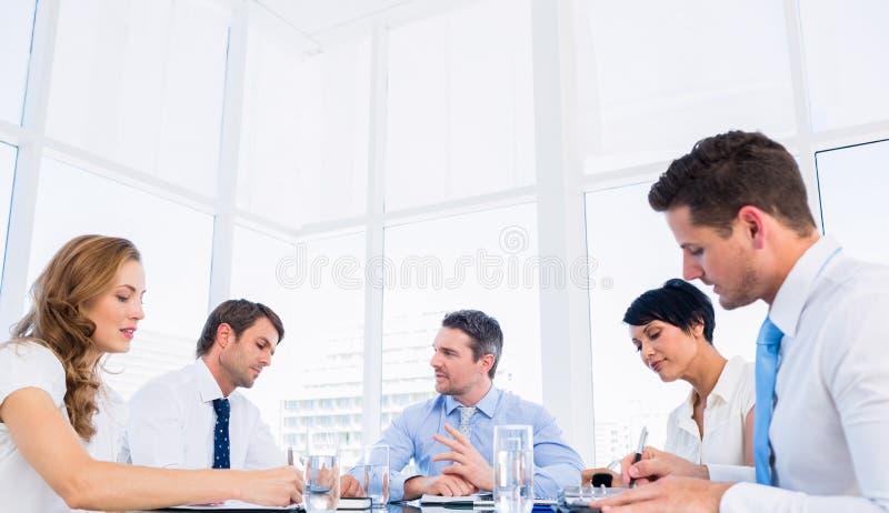 Führungskräfte, die um Konferenztisch sitzen stockfotos