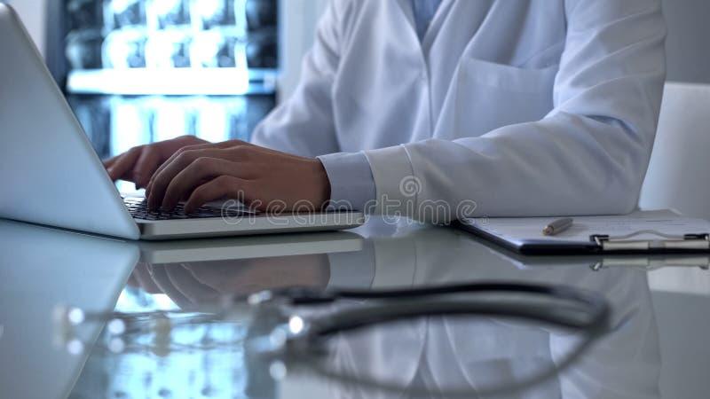 Füllende Daten Berufsdoktors in den on-line-Krankenblättern, arbeitend an Laptop stockfoto