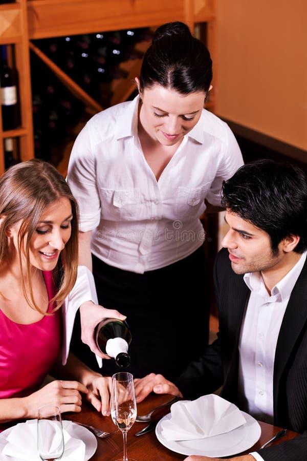 Füllende Gläser der Kellnerin mit Champagner stockfotos