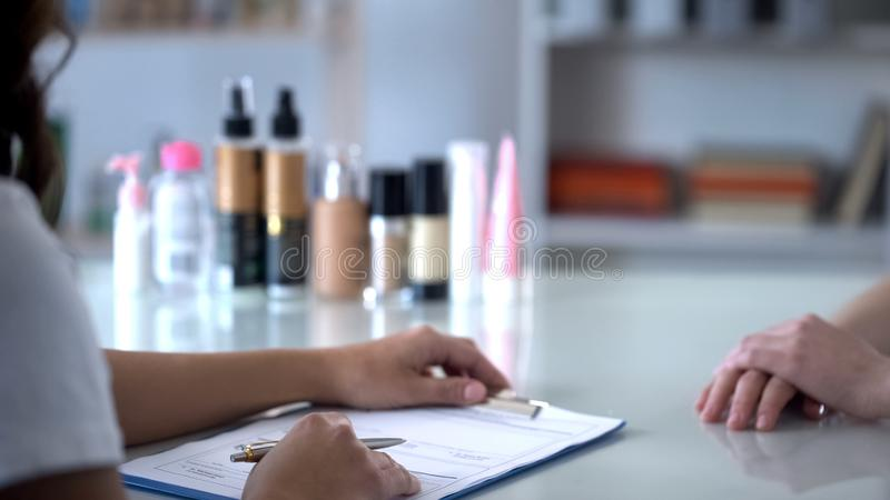 Füllende Kundenkarte des Kosmetikers vor der Ernennung von Verfahren, Sorgfalt für Kunden lizenzfreie stockfotografie