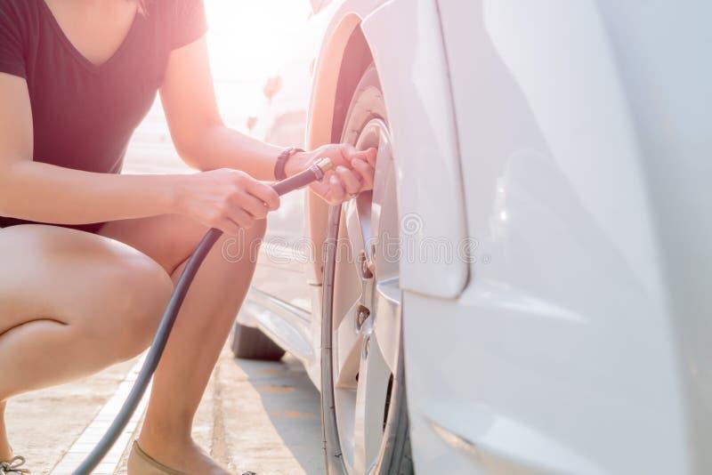 Füllende Luft des Fahrers in einen Autoreifen, Reifeninflation stockfotografie