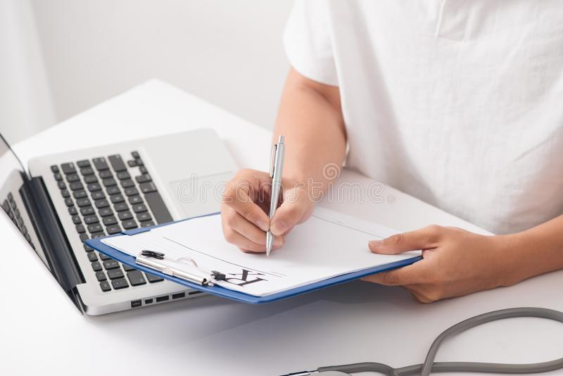 Füllende Patientenanamneseliste des Doktorhandgriffsilberstiftes am Klipp lizenzfreie stockbilder