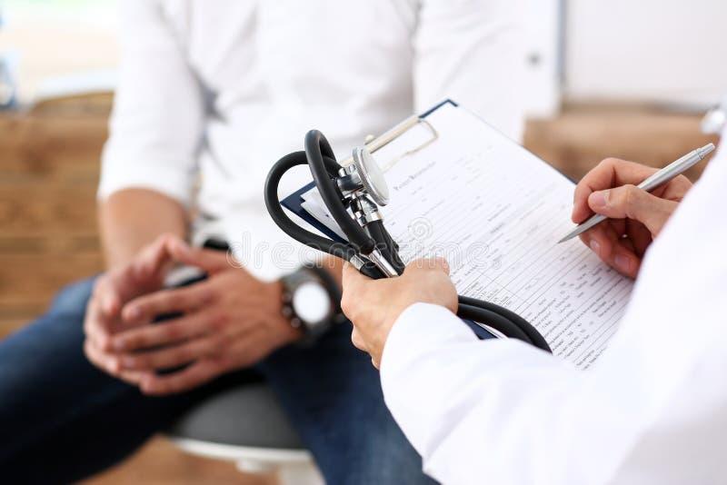 Füllende Patientenanamneseliste des männlichen Doktorhandgriffsilberstiftes stockfotografie