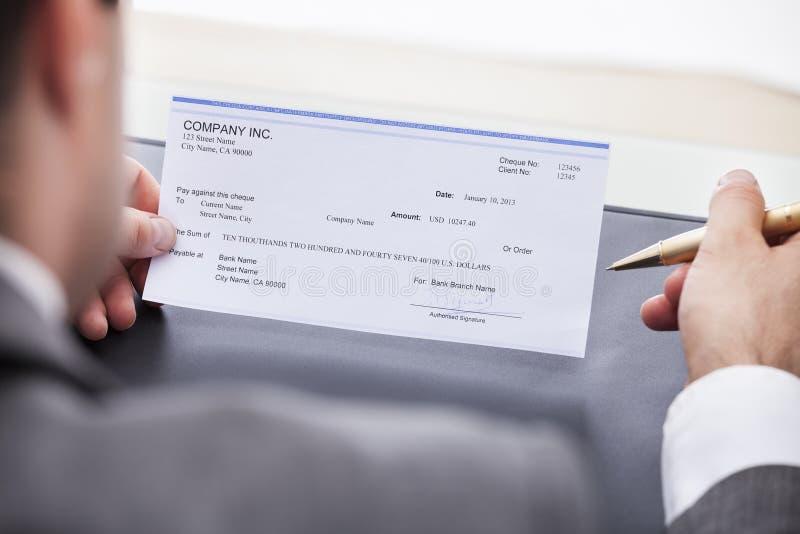 Füllender Scheck des Geschäftsmannes lizenzfreie stockfotos