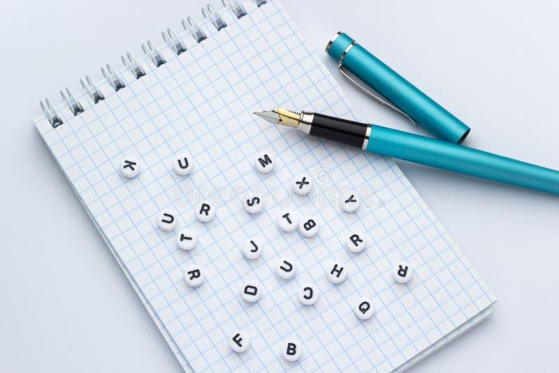 Füllfederhalter und Notizbuch mit Buchstaben auf einem weißen Hintergrund stockfoto