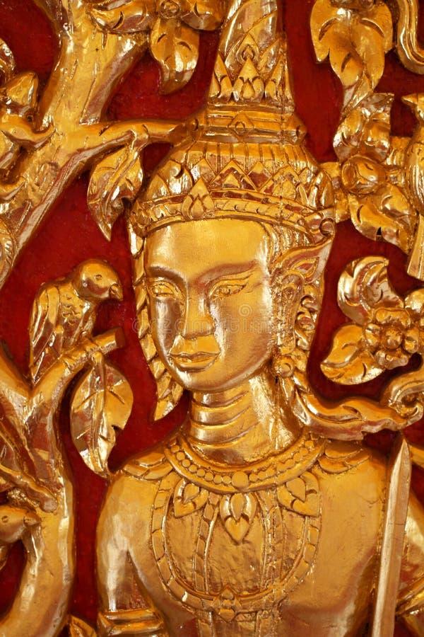 Füllte männliche thailändische Engelsstatue der Nahaufnahme mit Goldblatt mit roten Hintergründen, hölzernes in Handarbeit machen stockfoto