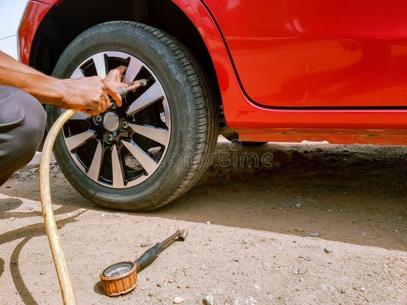 Füllung der Luft in einem hinteren Reifen eines Automobils, zum des Luftdrucks beizubehalten lizenzfreies stockfoto
