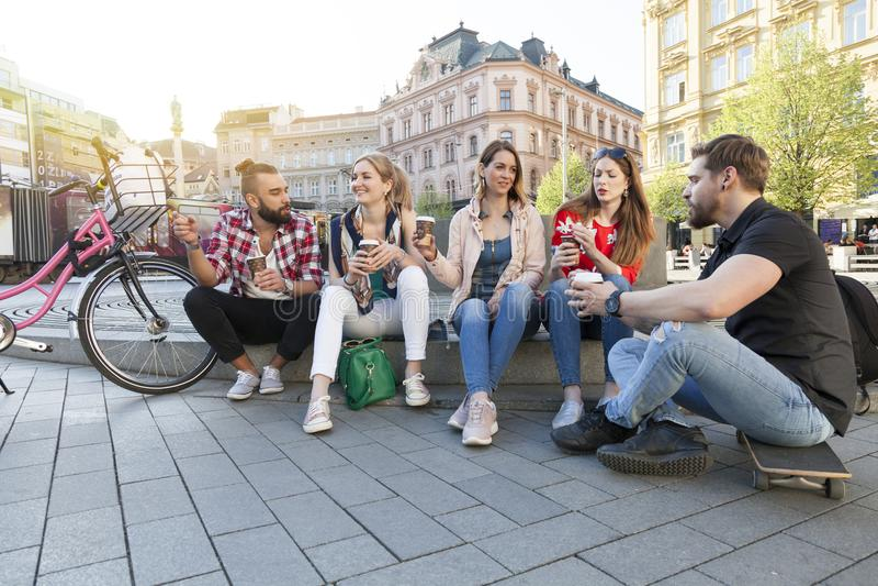 Fünf beste Freunde haben eine Versammlung in der Stadtstraße trinkend, Kaffee zum Mitnehmen wegzunehmen lizenzfreie stockfotos