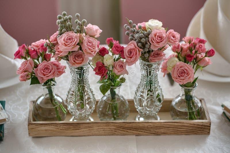 Fünf Blumensträuße von Rosen auf einer festlichen Hochzeitstafel im restaur stockbild