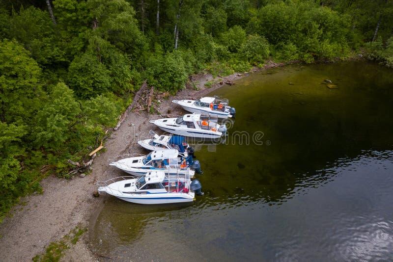 Fünf Boote, die auf dem Pier auf dem Teletskoe See in den Altai-Bergen nahe dem lokalen Markstein in der Erwartung stehen lizenzfreie stockfotos
