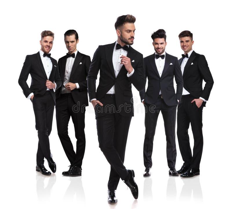 Fünf Bräutigame in den schwarzen tuxedoes mit nachdenklichem Führer in der Front stockbilder