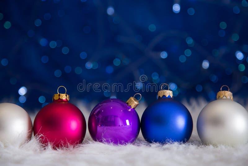 Fünf bunte Weihnachtsbälle auf weißem Pelz mit Girlande beleuchtet O stockfotografie
