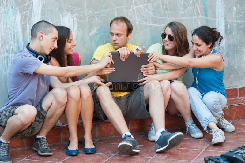 Fünf Freunde, die über einem Laptop kämpfen lizenzfreie stockfotos