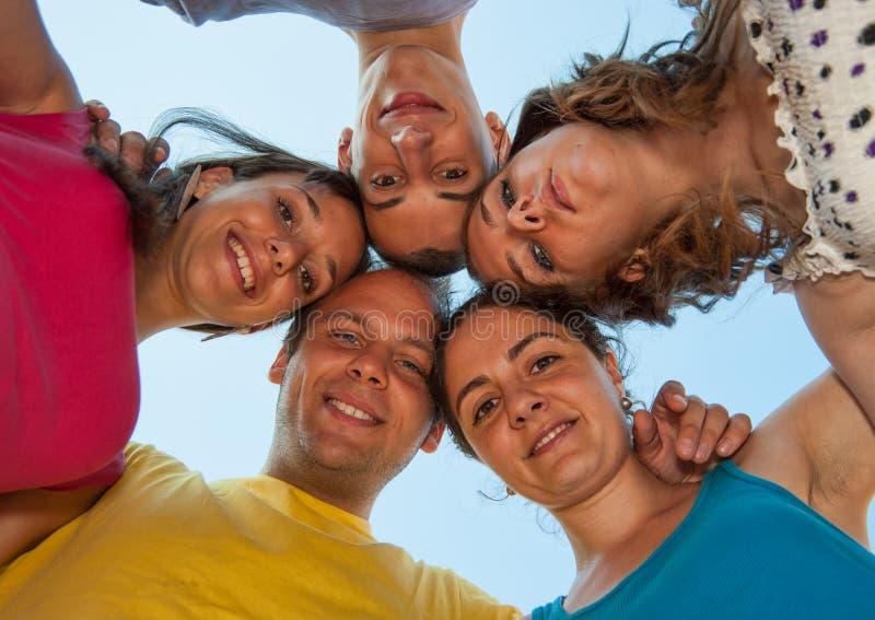 Fünf Freunde, die eine Umarmung teilen stockfotografie
