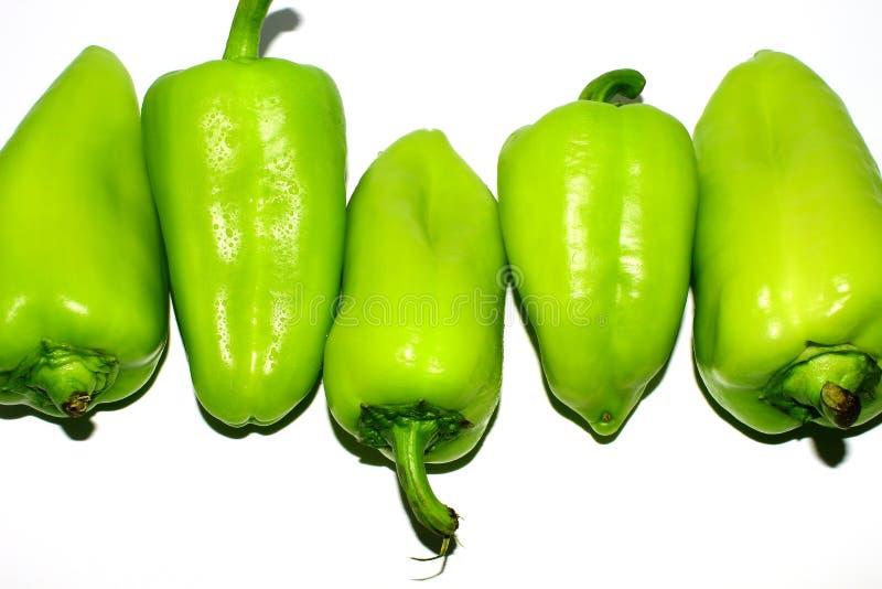 Fünf frische grüne Gemüsepaprikas mit Wassertropfen lizenzfreie stockfotos