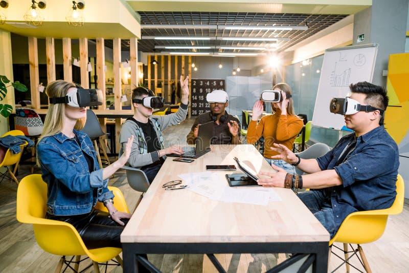 Fünf gemischtrassige junge Studenten, welche die Gläser der virtuellen Realität Innen - glückliche Menschen haben Spaß mit neue T stockfotos