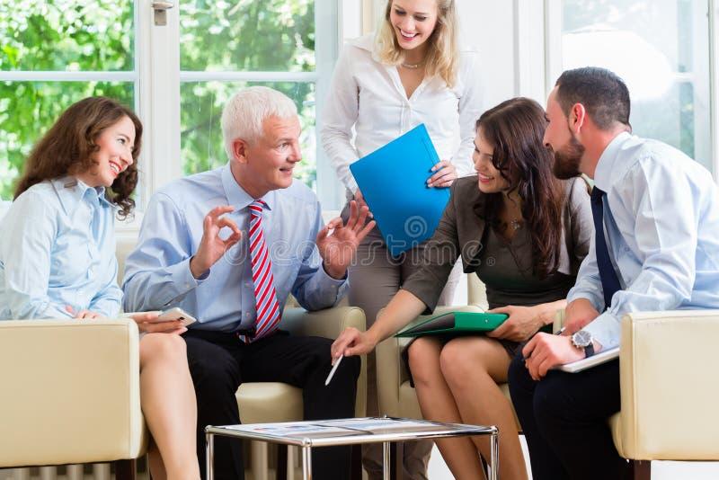 Fünf Geschäftsleute in der Teambesprechung, die Diagramme studiert lizenzfreie stockfotos