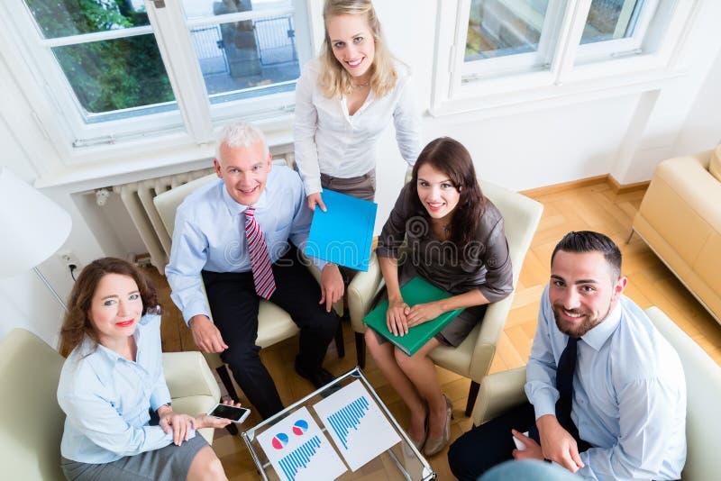 Fünf Geschäftsleute in der Teambesprechung, die Diagramme studiert stockfotografie