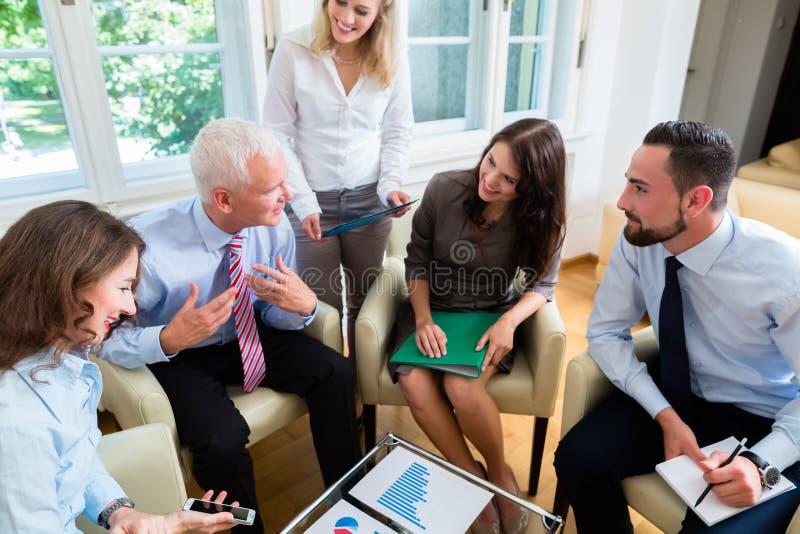 Fünf Geschäftsleute in der Teambesprechung, die Diagramme studiert stockbild
