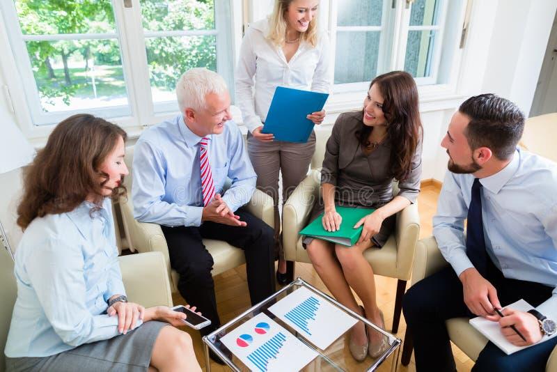 Fünf Geschäftsleute in der Teambesprechung, die Diagramme studiert stockfoto