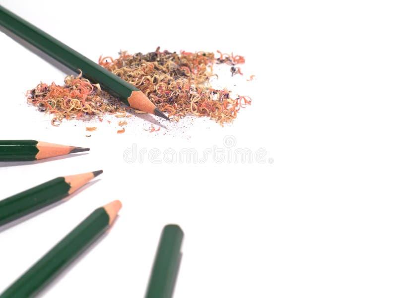 Fünf geschärft und unsharpened grüne Bleistifte mit Bleistiftsägemehl lizenzfreie stockfotos