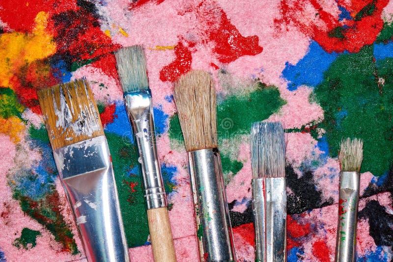 Fünf getragene heraus Bürsten von verschiedenen Größen auf der bunten rosa Palette lizenzfreie stockfotos
