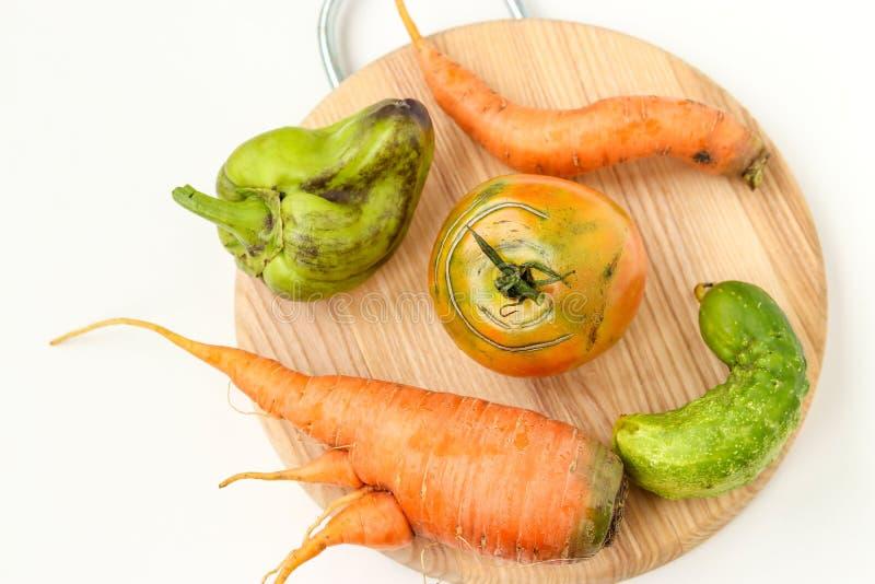 Fünf hässliches Gemüse: Karotten, Gurke, Pfeffer und Tomate auf hölzernem Brett auf weißem Hintergrund, hässliches Nahrungsmittel lizenzfreies stockfoto