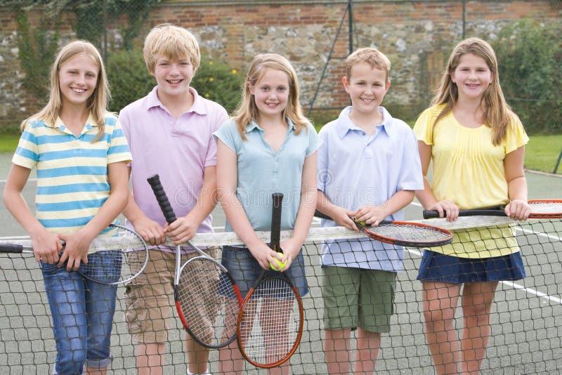 Fünf junge Freunde auf dem Tennisgerichtslächeln lizenzfreie stockfotografie