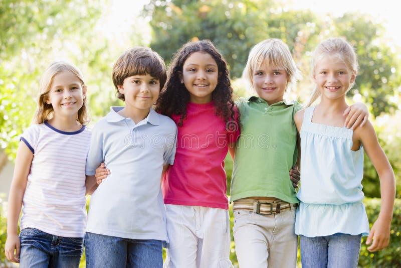 Fünf junge Freunde, die draußen lächelnd stehen stockbild