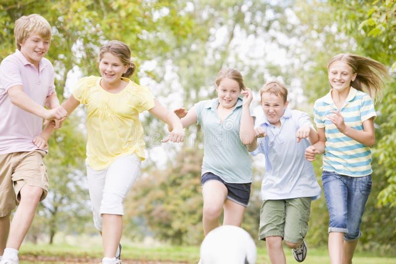 Fünf junge Freunde, die Fußball spielen stockbild
